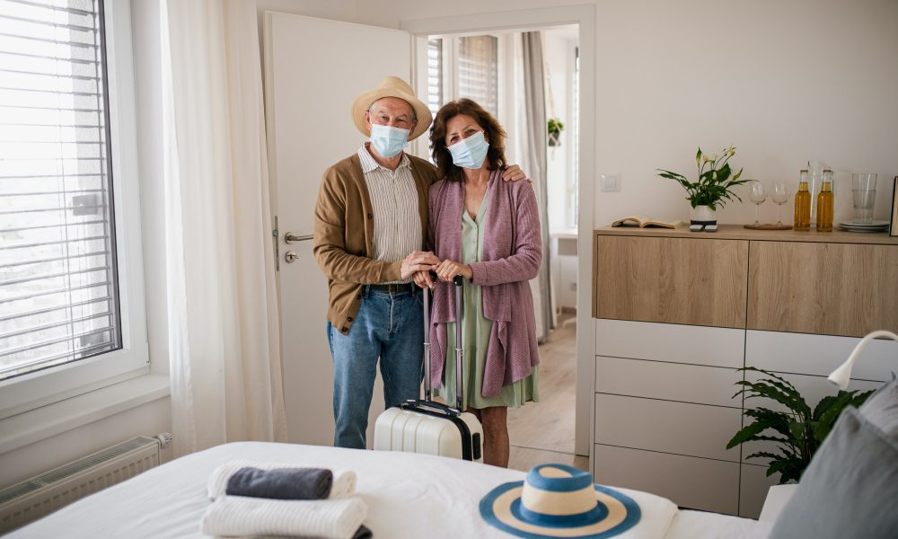 Senior couple arriving in hotel room, coronavirus, holiday and new normal concept